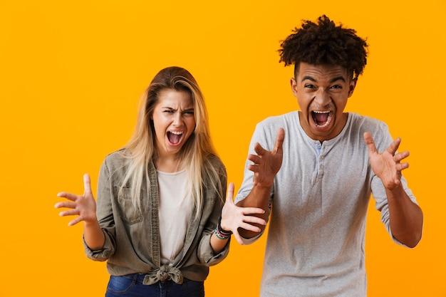 Кричащая молодая милая влюбленная пара позирует изолированной над желтой стеной