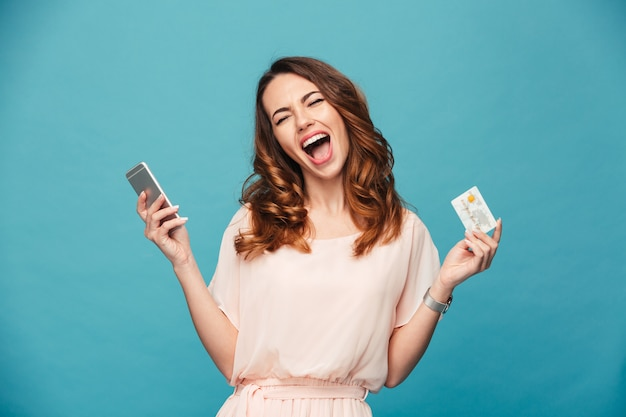 Screaming young lady using mobile phone holding credit card.