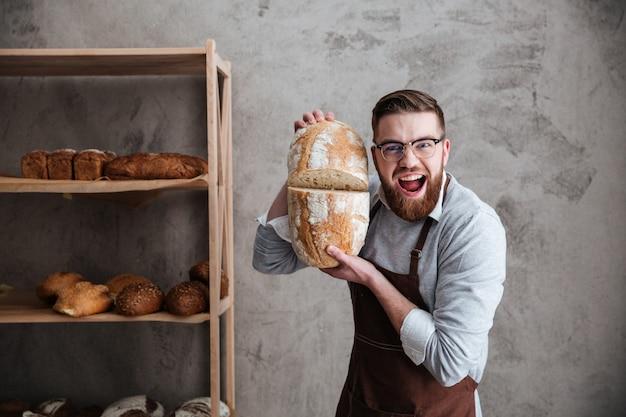 Кричащий пекарь молодого человека стоя на хлебопекарне держа хлеб