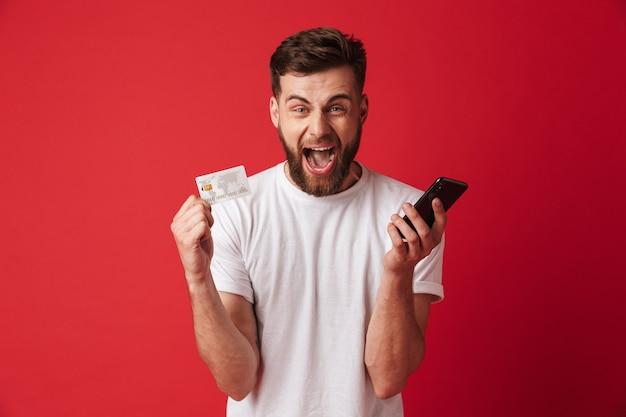 携帯電話とクレジットカードを保持している若い男の叫び。カメラを探しています。
