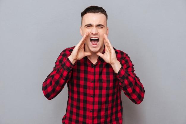 Кричащий молодой человек в схватке за руки возле лица