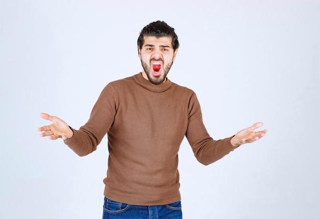 立って手を上げてポーズをとる若い男のモデルを叫びます。