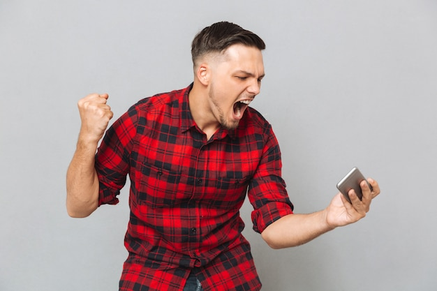 Screaming young man using mobile phone