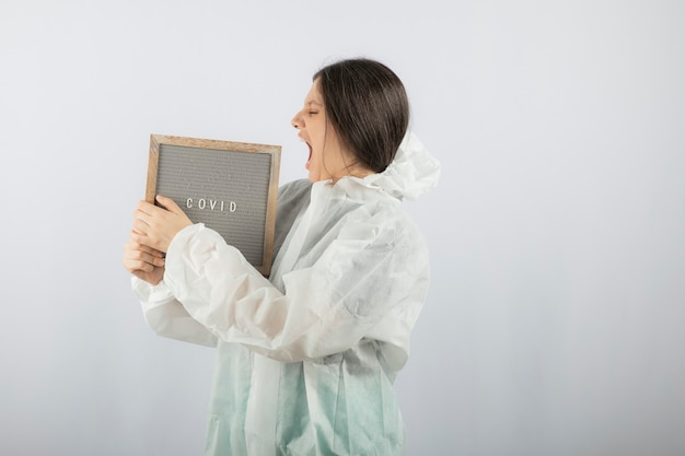 Screaming young woman model in defensive lab coat.