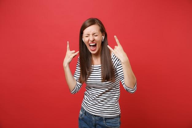 빨간 벽 배경에서 격리된 음악을 듣고 헤비메탈 록 뿔 기호를 묘사한 무선 이어폰을 들고 소리를 지르는 젊은 여성. 사람들은 진심 어린 감정, 라이프 스타일 개념입니다. 복사 공간을 비웃습니다.