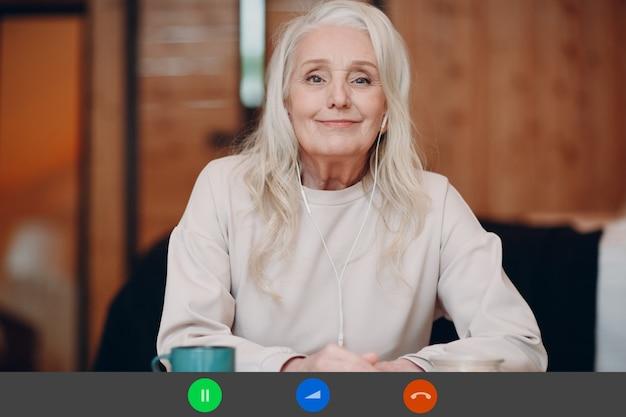 Экран приложения: улыбающаяся пожилая женщина сидит за столом с ноутбуком и разговаривает по видеосвязи с другом или коллегой, счастливая зрелая женщина с чашкой чая или кофе, говорящая онлайн на веб-камеру в помещении