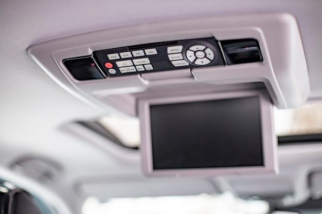 Screen m multimedia system control panel on white ceiling of a modern car. close-up
