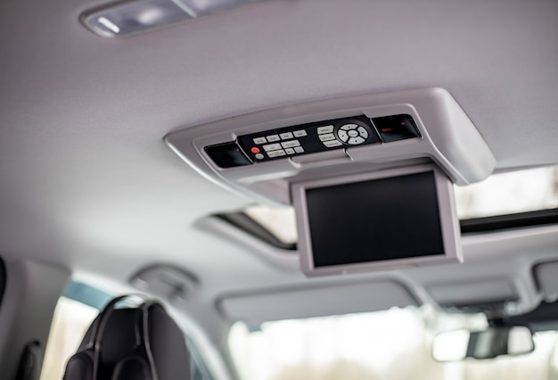 Screen multimedia system control panel. interior detail of modern luxury car dashboard with big display and light button switch on ceiling. screen multimedia system