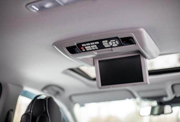 画面マルチメディアシステムのコントロールパネル。天井に大きなディスプレイとライトボタンスイッチを備えたモダンな高級車のダッシュボードのインテリアディテール。スクリーンマルチメディアシステム