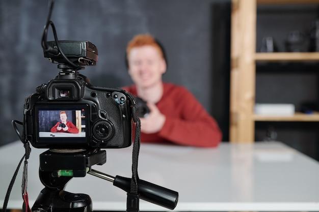 Экран видеокамеры с молодым мужским влогером или фотографом, держащим фотоаппарат во время съемки в студии