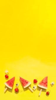 Заставка, фон для рассказов, баннер ломтиков арбуза на палочках, кубиков льда и клубники на ярко-желтом фоне. копировать пространство.