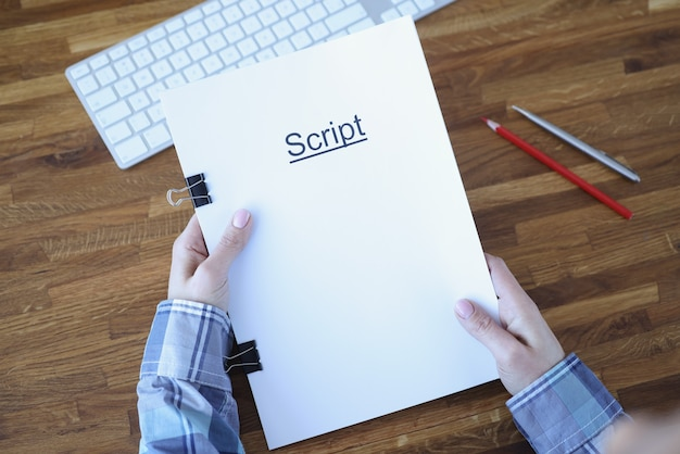 Screenwriter holds folder of documents labeled script. development of plots for films and