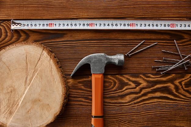 나무 테이블에 못, 망치 및 측정 테이프를 조이십시오. 전문 도구, 목수 장비, 패스너, 고정 및 나사 조임 도구