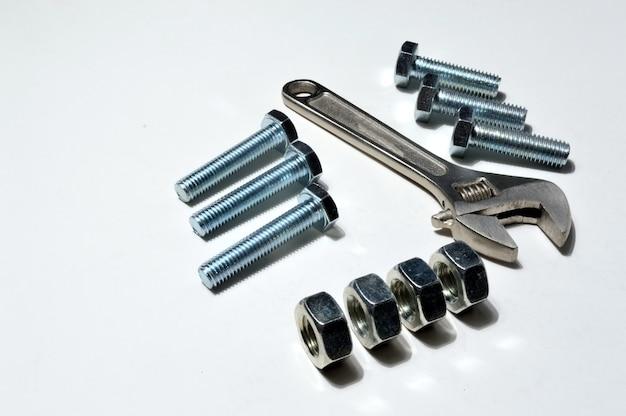 Винт-гайка разных размеров, болты и разводной ключ