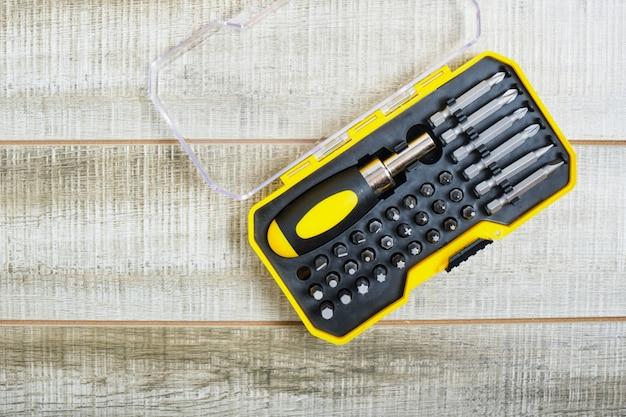 Отвертка и насадки в пластиковом ящике, место для копирования, насадки для отверток на деревянной поверхности