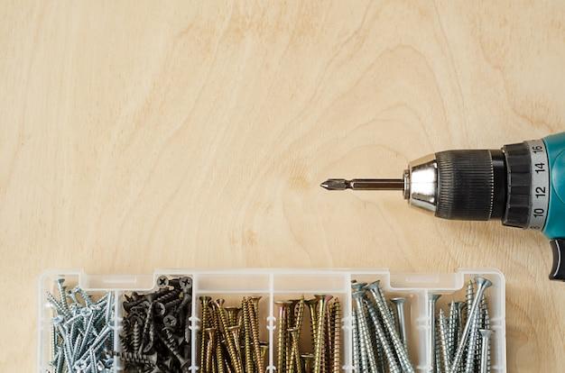 ドライバーと木製のテーブル、上面図、コピースペースのボックスにさまざまなサイズのネジ。仕事のための男性の大工道具