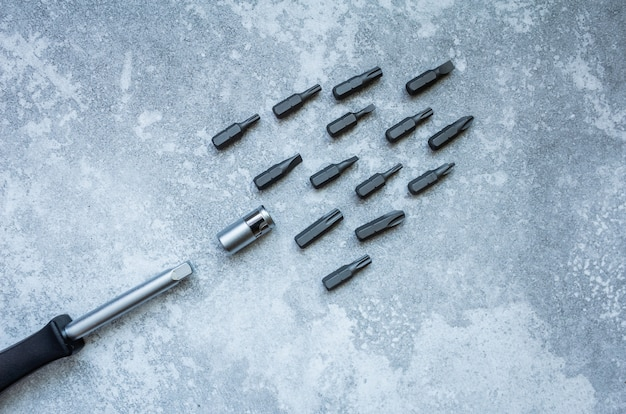 Screwdriver and screws on gray background.