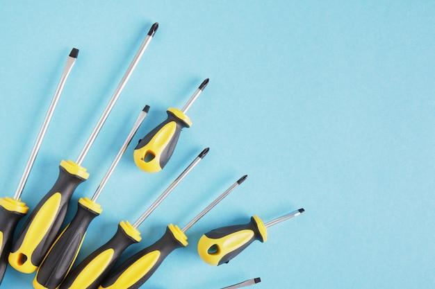 Набор отверток на синем фоне, вид сверху, копирование пространства, многие отвертки с черными и желтыми ручками
