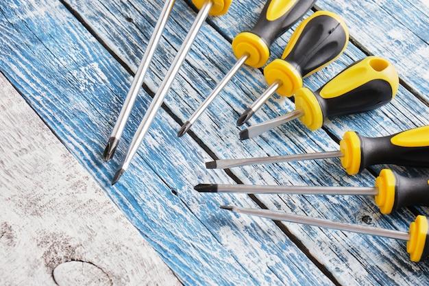 Набор отверток на деревянном фоне, вид сверху, копирование пространства, многие отвертки на фоне синих и серых старых досок