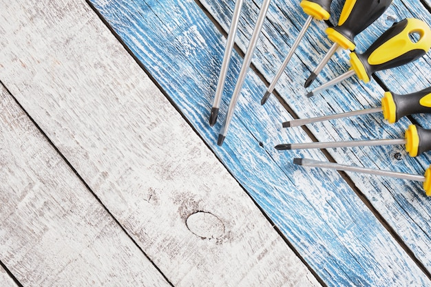 Screwdriver set on a wooden background top view copy space many screwdrivers on blue and gray old planks background