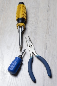 Screwdriver tool and pliers lie on a light-colored countertop.