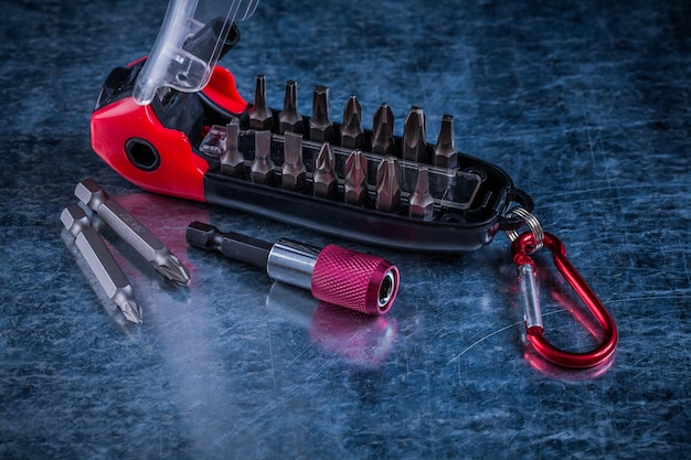 Screwdriver with interchangeable bits on scratched metallic background construction concept