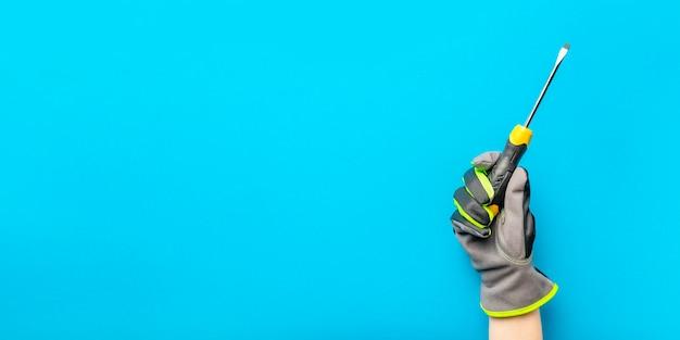 ドライバー。青のモノクロの背景に電気技師の手に黄色と黒のドライバー。修理およびインストールツール。建設トピックのデザインと印刷のためのバナー。