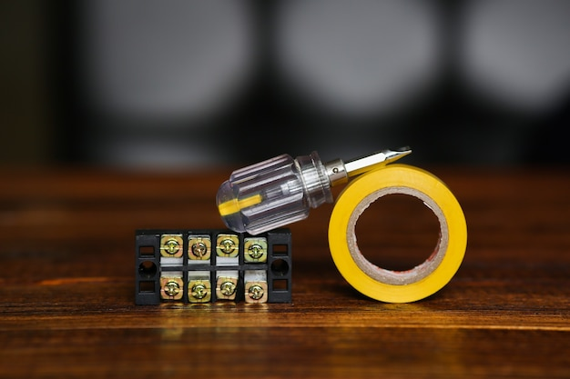 ドライバー、黄色の電気テープ、ワイヤーコネクター、端子台。電気技師のセット。高品質の写真
