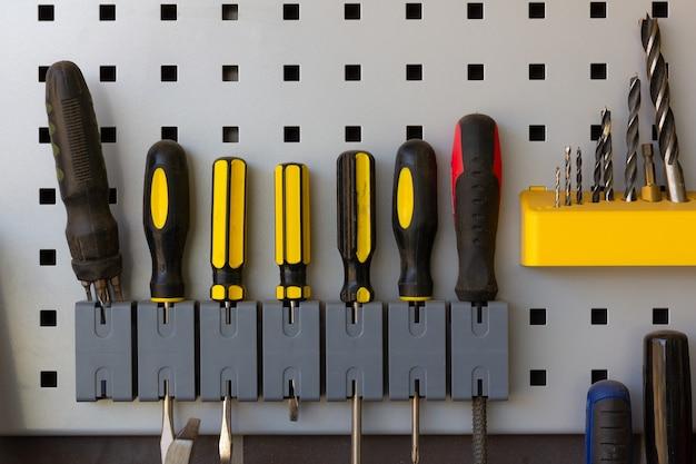 수리점 벽 산업 작업 장비 개념에 배치된 스크루드라이버 드릴 비트 및 도구