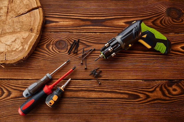 Screwdrivers and self tapping screws on stump, closeup. professional instrument, carpenter equipment, woodwork tools