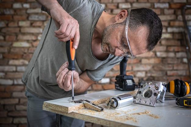大工の仕事であるドライバーを使用して、セルフタッピングネジを木片の金属製の固定穴にねじ込みます。