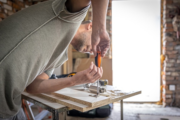 목수의 작업인 스크루드라이버를 사용하여 셀프 태핑 나사를 나무 스트립의 금속 고정 구멍에 조입니다.