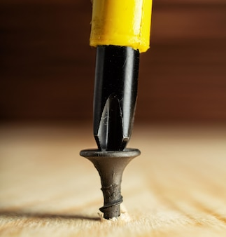 Screwing screw into wooden plank, joinery and construction work close up.
