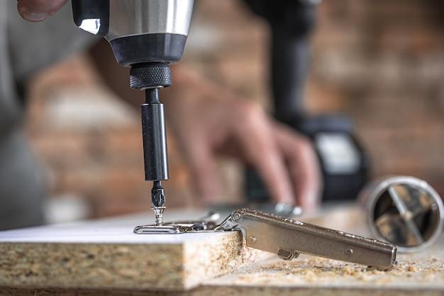 Avvitare una vite autofilettante in un foro di fissaggio metallico su un listello di legno usando un cacciavite, opera di un falegname.