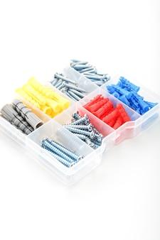 투명한 플라스틱 상자에 다양한 크기, 유형 및 색상의 나사와 다웰. 상단에서보기