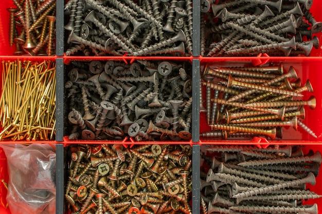 플라스틱 도구 상자(하드웨어 정리함)에 있는 나사, 볼트, 너트 및 기타 목수 재료. 평평한 평면도. 재고 사진.