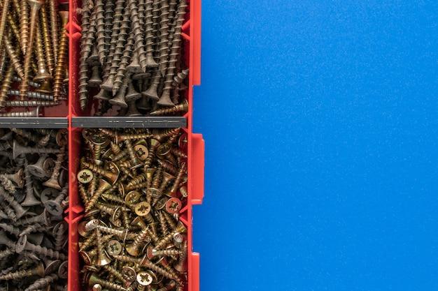 플라스틱 도구 상자(하드웨어 정리함)에 있는 나사, 볼트, 너트 및 기타 목수 재료. 텍스트에 대한 카피스페이스가 있는 평평한 평면도. 재고 사진.