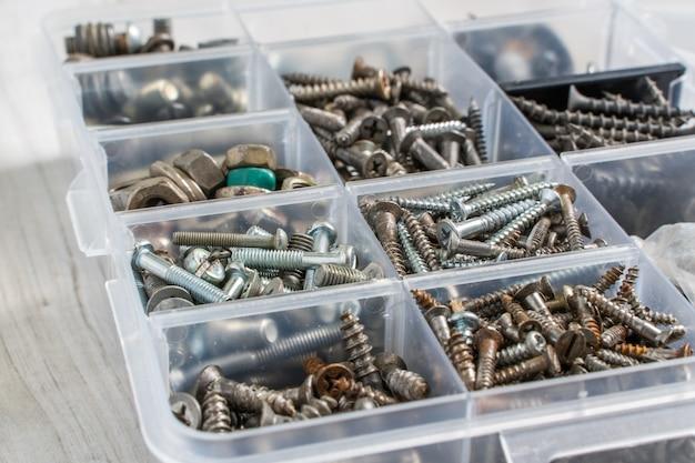 플라스틱 도구 상자(하드웨어 정리함)에 있는 나사, 볼트, 너트 및 기타 목수 재료. 재고 사진.