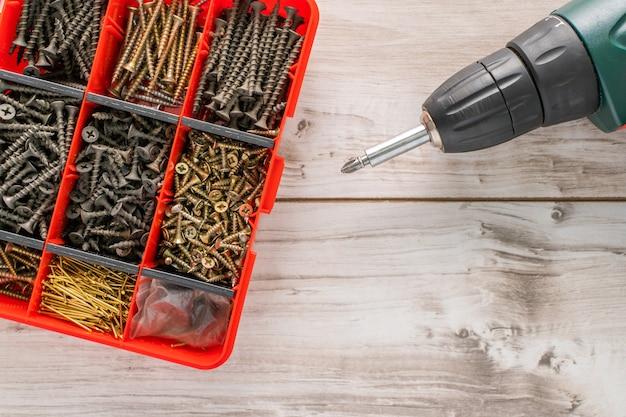 스크루드라이버가 있는 플라스틱 도구 상자(하드웨어 정리함)에 나사, 볼트, 너트 및 기타 목수 재료. 텍스트에 대한 카피스페이스가 있는 평평한 평면도. 재고 사진.