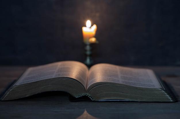 나무 테이블에 성경과 촛불