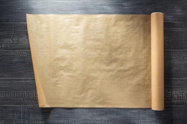 Свиток коричневой бумаги на деревянной текстуре фона