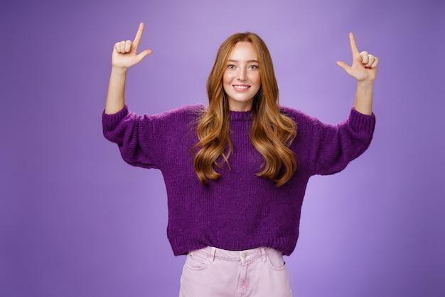 Прокрутите вверх и увидите классное место для копирования. портрет счастливой привлекательной и дружелюбной молодой женщины имбиря с веснушками в теплом фиолетовом свитере, поднимающем руки, указывающие вверх как место для показа.