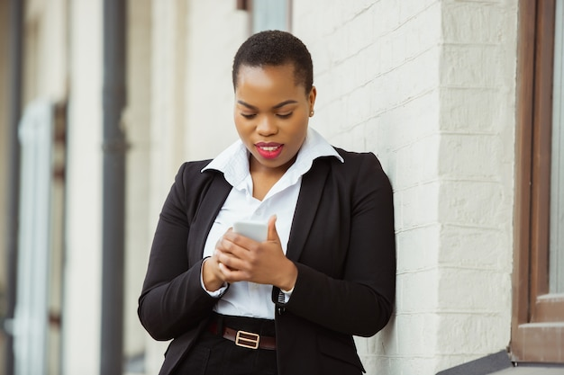 Scrolling phone africanamerican businesswoman in office attire smiling looks confident