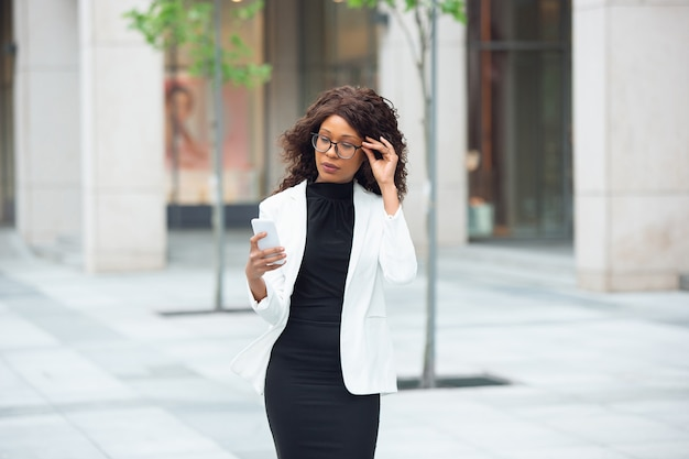 Scrolling phone chatting africanamerican businesswoman in office attire smiling looks