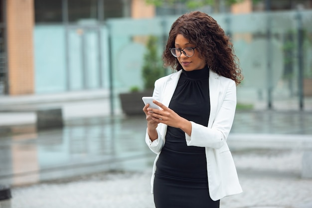 Scrolling phone chatting africanamerican businesswoman in office attire smiling