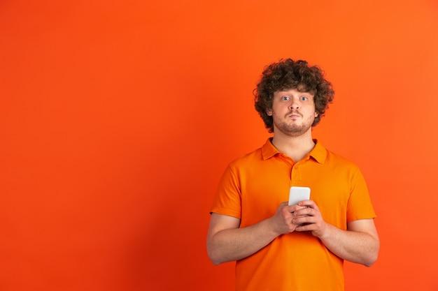 Прокрутка смартфона. монохромный портрет кавказского молодого человека на оранжевой стене. красивая мужская фигурная модель в стиле casual. понятие человеческих эмоций, выражения лица, продаж, рекламы.