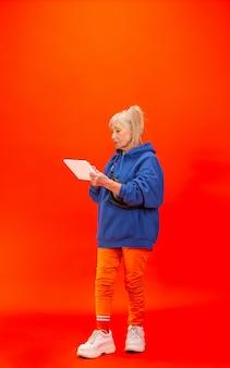 スクロールタブレット。明るいオレンジ色に分離された超流行の服装の年配の女性