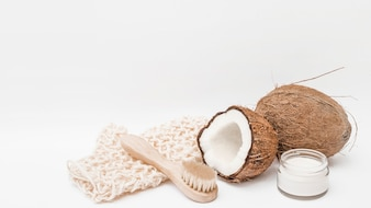 Scrub glove; brush; coconut and moisturizing cream on white background