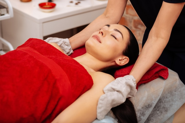 Scrubbing client. peaceful good-looking lady sleeping while master caring her skin with special gloves