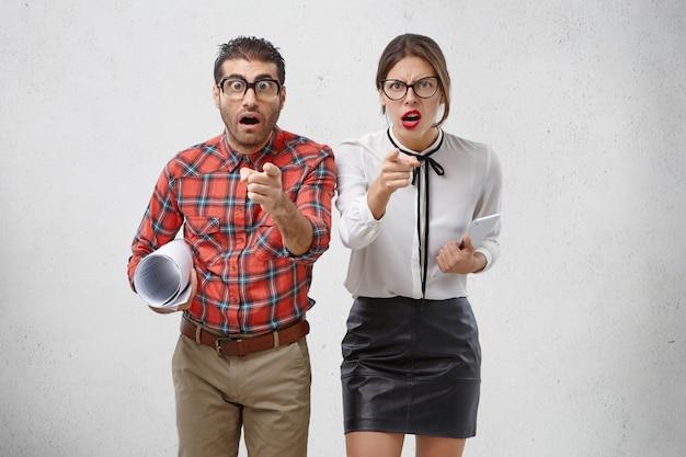 Скрупулезные предприниматели-женщины и мужчины указывают на вас и смотрят гневно или возбужденно.